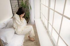 Opinión superior la mujer asiática deprimida que se sienta en cama Foto de archivo