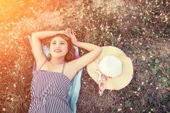 Opinión superior la mujer atractiva joven que miente en la hierba que acerca a su mirada del sombrero Foto de archivo libre de regalías