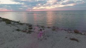 Opinión superior la mujer con maquillaje brillante en un baile rosado del vestido con las bombas de humo en el banco del río La d metrajes