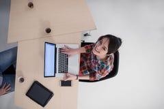 Opinión superior la mujer de negocios joven que trabaja en el ordenador portátil foto de archivo