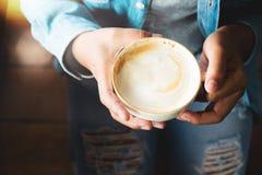 Opinión superior la mujer en taza del control de los vaqueros de café caliente Fotografía de archivo