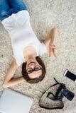 Opinión superior la mujer feliz alegre que miente en piso con la cámara, gla Foto de archivo libre de regalías
