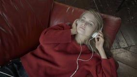 Opinión superior la mujer joven atractiva en auriculares que escucha la música y que sonríe mientras que miente en el sofá en cas metrajes
