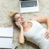Opinión superior la mujer joven que charla en el teléfono en casa Foto de archivo