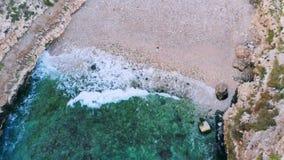 Opinión superior la mujer joven que miente en Pebble Beach cerca de ondas del mar almacen de metraje de vídeo