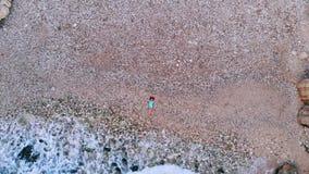Opinión superior la mujer joven que miente en Pebble Beach cerca de ondas del mar metrajes