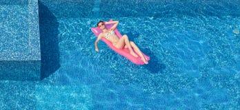 Opinión superior la mujer que broncea hermosa en piscina imagen de archivo