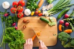 Opinión superior la mujer que cocina la comida sana: verdura del corte ingred imagenes de archivo