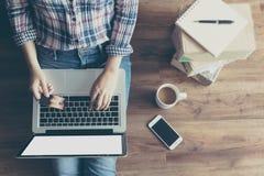 Opinión superior la mujer que hace compras en línea con la tarjeta de crédito vía el ordenador portátil del hogar en piso de made imágenes de archivo libres de regalías