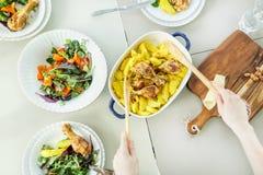 Opinión superior la mujer que prepara el pollo asado con el acompañamiento de la patata Imagen de archivo libre de regalías