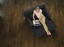 Opinión superior la mujer que usa el ordenador portátil en el sofá fotos de archivo libres de regalías