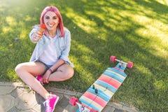 Opinión superior la mujer sonriente hermosa europea con el pelo rosado con helado a disposición en parque en fondo de la hierba v fotos de archivo