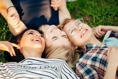 Opinión superior los amigos elegantes que miran la cámara y que sonríen mientras que miente en hierba Foto de archivo