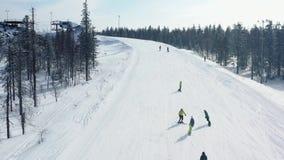 Opinión superior los esquiadores y los snowboarders que montan en la montaña cantidad Estación de esquí con resto activo en l almacen de metraje de vídeo