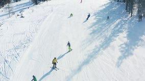 Opinión superior los esquiadores y los snowboarders que montan en la montaña cantidad Estación de esquí con resto activo en l almacen de video
