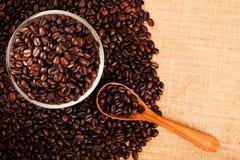 Opinión superior los granos de café con el fondo de la arpillera y el espacio de la copia Foto de archivo