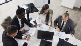 Opinión superior los hombres de negocios diversos jovenes que se encuentran en la tabla de la sala de reunión que discute informe almacen de video