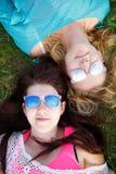 Opinión superior mujeres felices en las gafas de sol que mienten en hierba Imagen de archivo