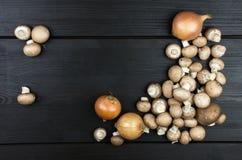 Opinión superior setas y cebollas frescas en fondo de madera oscuro Imágenes de archivo libres de regalías