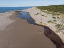 Opinión superior sobre bosque y el río que fluye en la costa costa del mar al mar Foto de archivo