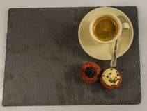 Opinión superior sobre dos magdalenas dulces, la zarzamora y el chocolate cremoso Imagen de archivo libre de regalías