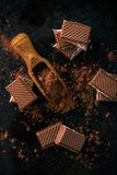 Opinión superior sobre el cacao en cuchara y pocos pedazos de chocolate Imagen de archivo libre de regalías