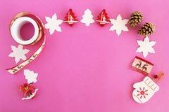 Opinión superior sobre el marco de decoraciones de la Navidad roja y blanca y de conos del pino en el fondo rosado Foto de archivo