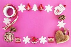 Opinión superior sobre el marco de decoraciones de la Navidad y de conos de madera rojos y blancos del pino en el fondo rosado Foto de archivo