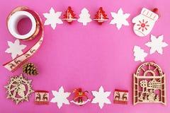 Opinión superior sobre el marco de decoraciones de la Navidad y del cono de madera rojos y blancos del pino en el fondo rosado Foto de archivo libre de regalías