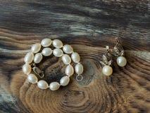 Opinión superior sobre el sistema elegante de braclet de la perla y los pendientes en fondo de madera Cierre para arriba Imagenes de archivo