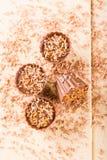 Opinión superior sobre el tablero de madera ligero con cuatro magdalenas del chocolate Imagen de archivo libre de regalías