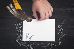 Opinión superior sobre la mano que sostiene el martillo, clavos dispersados, hoja de papel en blanco en la tabla de madera negra imágenes de archivo libres de regalías