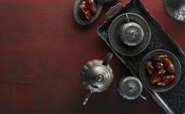 Opinión superior sobre la placa de plata con las frutas de la fecha y las tazas de café en el fondo de madera rojo oscuro Fondo d foto de archivo libre de regalías