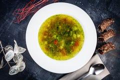 Opinión superior sobre la sopa italiana fresca del minestrone en el cuenco blanco servido en fondo oscuro Comida puesta plana par fotografía de archivo