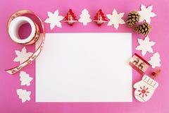 Opinión superior sobre las decoraciones de la Navidad, los conos del pino y la hoja de papel blanca en el fondo rosado Foto de archivo libre de regalías