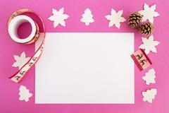 Opinión superior sobre las decoraciones de la Navidad y la hoja de papel blanca en el fondo rosado Fotografía de archivo