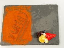Opinión superior sobre las frutas y la palabra deliciosa en la placa de piedra negra Foto de archivo
