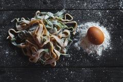 Opinión superior sobre las pastas hechas en casa crudas con la harina y el huevo crudo sobre la tabla de madera vieja imagen de archivo