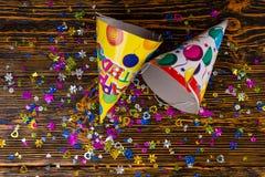 Opinión superior sobre los casquillos del cumpleaños y el confeti festivo colorido Foto de archivo libre de regalías