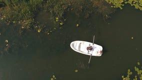 Opinión superior sobre pares cariñosos en un barco en el lago metrajes