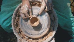 Opinión superior sobre trabajo de manos del ` s del alfarero con la arcilla en una rueda del ` s del alfarero almacen de video