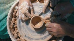 Opinión superior sobre trabajo de manos del ` s del alfarero con la arcilla en una rueda del ` s del alfarero Cámara lenta metrajes