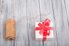 Opinión superior sobre una bola de hilos y de una caja de regalo en el fondo de madera Imágenes de archivo libres de regalías