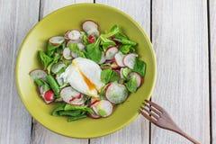 Opinión superior sobre una ensalada del rábano con el huevo escalfado con la bifurcación de madera Imagenes de archivo