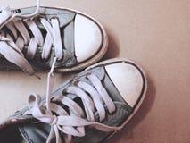 Opinión superior sucia de zapatos de la exhibición azul de las zapatillas de deporte en backgroun marrón Imagen de archivo