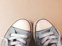 Opinión superior sucia de zapatos de la exhibición azul de las zapatillas de deporte en backgroun marrón Foto de archivo libre de regalías