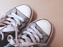 Opinión superior sucia de zapatos de la exhibición azul de las zapatillas de deporte en backgroun marrón Imágenes de archivo libres de regalías