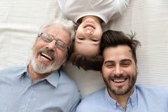 Opini?n superior tres generaciones felices de sonrisa de los hombres foto de archivo libre de regalías