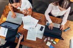 Opinión superior tres mujeres que trabajan con los documentos usando los ordenadores portátiles que se sientan en el escritorio imagen de archivo libre de regalías