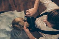 Opinión superior un cliente rubio de la peluquería de caballeros Él está consiguiendo su perfec foto de archivo